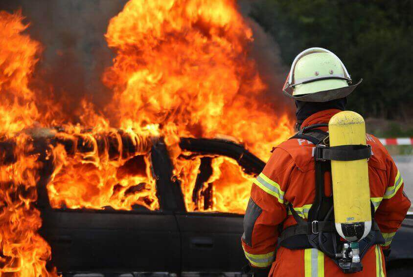 Fireman blowing out a fire on a car after a bad crash